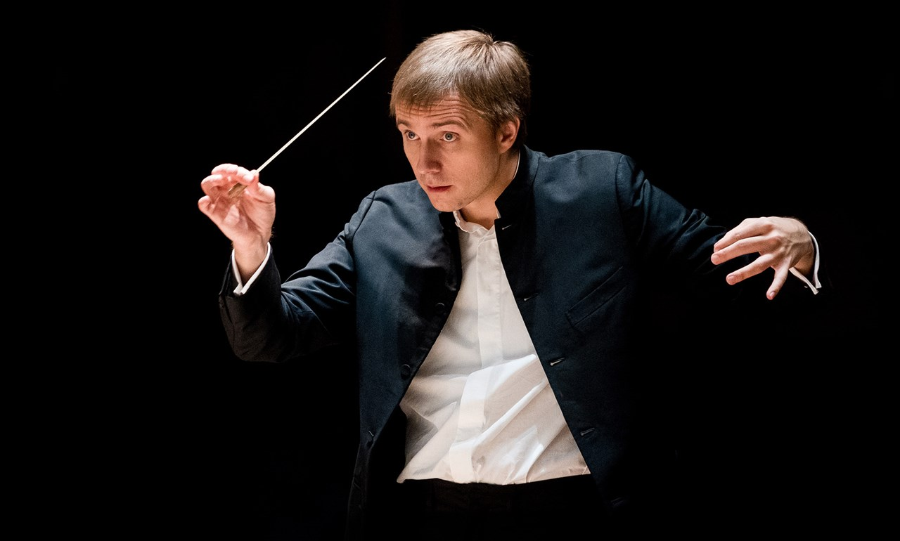 dark background with conductor holding baton dressed in a suit