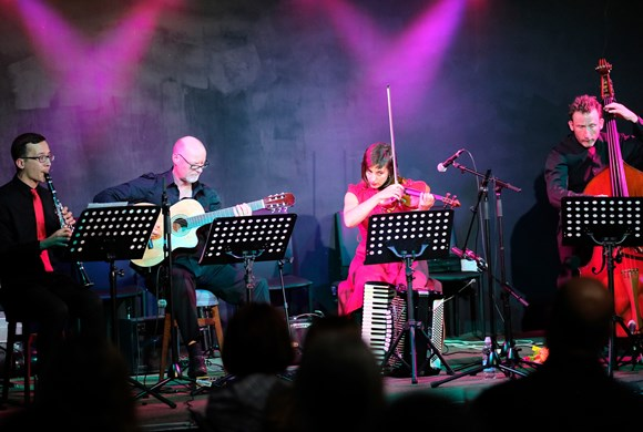 quartet on stage with pink lights