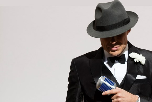 singer in suit and hat looks down holding a microphone