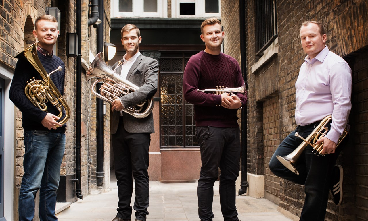 4 young males holding brass instrument sare standing in an alley way looking at the camera