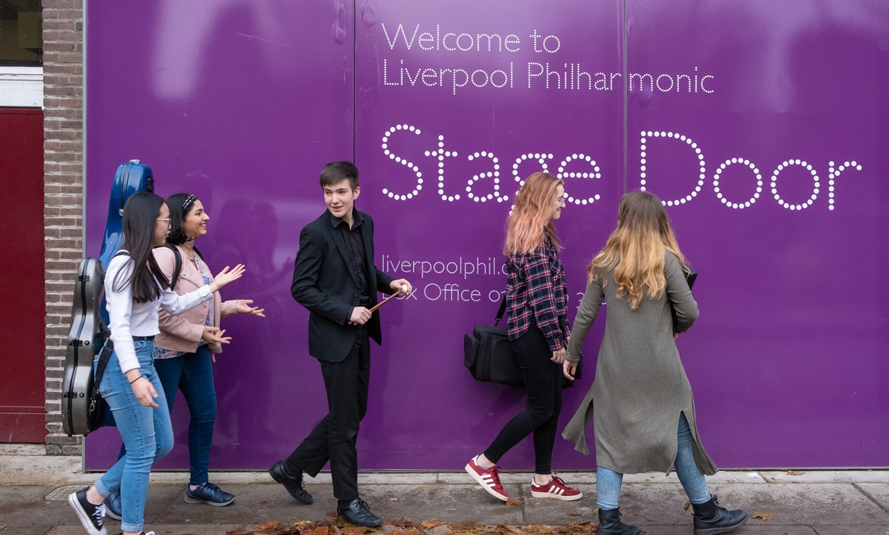 smiling youth company members in fronr of a purple stage door